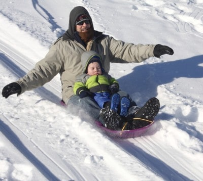 father and son sledding down hill in geauga county