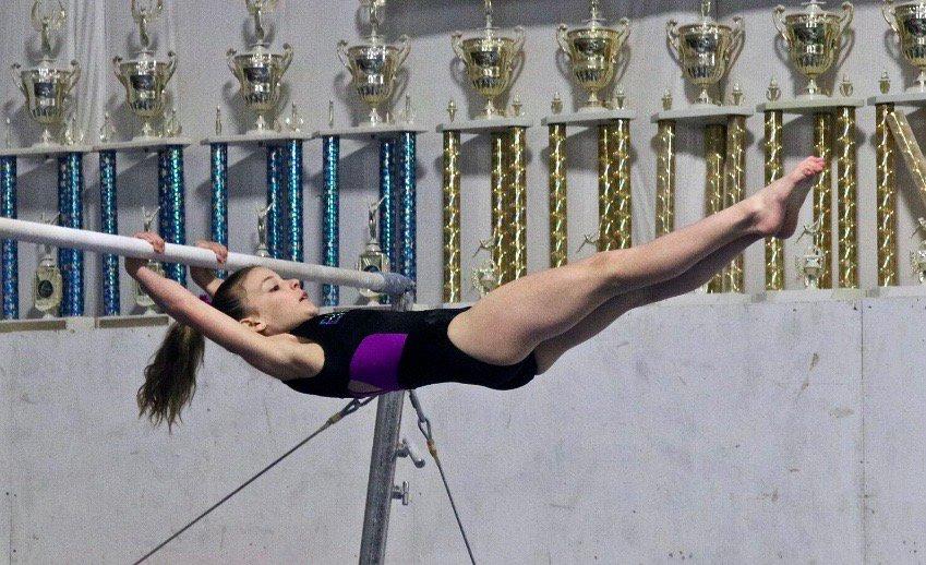 girl swinging on high bar