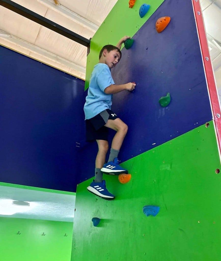 boy climbing warp wall