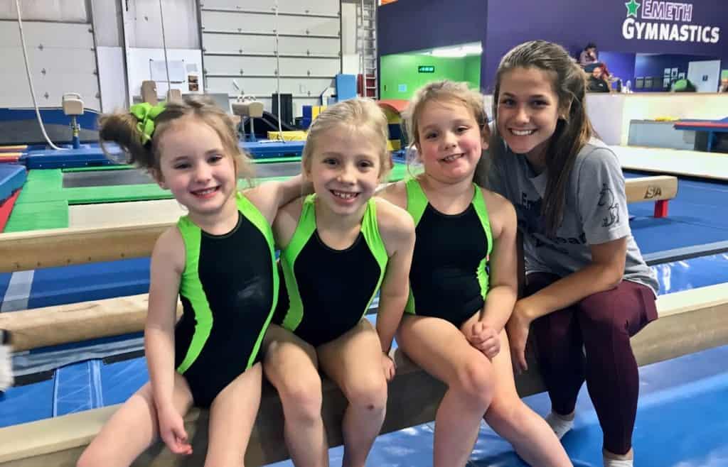 gymnastics coach with three girls